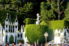 Hedges and Exterior panels of It's a Small World, Disneyland Fantasyland, Anaheim, California. Boarding queue decorated with topiary backed by a large, flat Stock Image