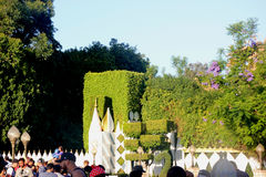 Hedges and Exterior panels of It's a Small World, Disneyland Fantasyland, Anaheim, California. Boarding queue decorated with topiary backed by a large, flat Stock Images