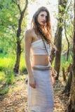 Hednisk kvinna som undrar nyfiket till och med skogen Royaltyfria Bilder