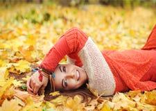 Heeft de Yound leuke vrouw een rust die in de herfstpark liggen stock afbeeldingen