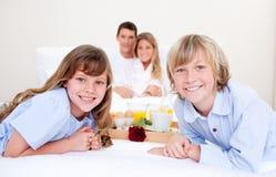 Heel familie die ontbijtzitting op bed heeft stock afbeeldingen