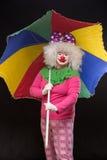 Heel goede grappige clown met een multi-colored paraplu op een zwarte Royalty-vrije Stock Foto's