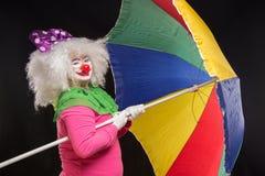Heel goede grappige clown met een multi-colored paraplu op een zwarte Royalty-vrije Stock Afbeeldingen