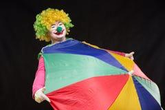 Heel goede grappige clown met een multi-colored paraplu op een zwarte Royalty-vrije Stock Fotografie