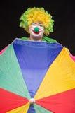 Heel goede grappige clown met een multi-colored paraplu op een zwarte Royalty-vrije Stock Foto