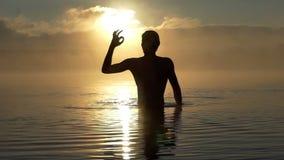 Heel heft de mens omhoog water in een meer bij zonsondergang in slo-mo op stock video