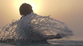 Heel mensenspelen met meerwateren in de zomer bij zonsondergang in slo-mo stock video