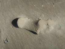 Heel spur, print of a foot in the snad of the beach royalty free stock image