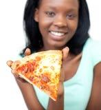 Heel tienermeisje dat een plak van pizza toont royalty-vrije stock fotografie