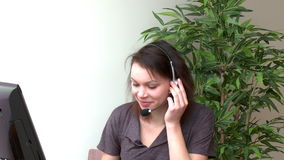 Heel vrouw met hoofdtelefoon bij het werken bij een computer stock videobeelden