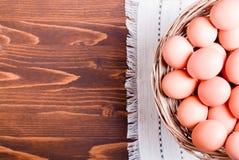 Heel wat bruine eieren in een rieten mand op een bruine mening van de lijstbovenkant Royalty-vrije Stock Foto