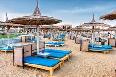 Heel wat chaise zitkamers met blauwe matrassen op een luxueus strand Paraplu's voor bescherming tegen de zon royalty-vrije stock afbeelding