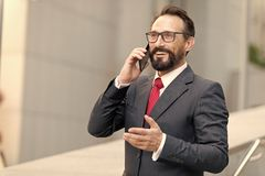 Heel wat! De gebaarde zakenman spreekt telefonisch en lacht Mening van een Jonge aantrekkelijke bedrijfsmens in glazen die smartp stock afbeeldingen