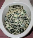 Heel wat dollars in een toiletkom Geldtoilet royalty-vrije stock fotografie