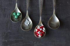 Heel wat gekleurde pillen en geneesmiddelen, vitaminen, capsules in een lepel op een donkere achtergrond stock afbeelding