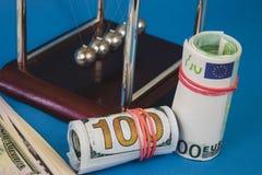 heel wat gelddollars en Newton-ballen op een blauwe achtergrond stock foto's