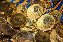 Heel wat gouden medailles met gele linten op een zilveren dienblad, toekenning van kampioenen, sportverwezenlijkingen, eerste pla Stock Afbeelding