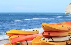 Heel wat heldere oranje plastic boten liggen op het strand Etretat, Normandië Stock Fotografie