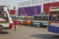 Heel wat Indische heldere multi-colored bussen die bij het busstation op de achtergrond van mensen worden geparkeerd stock foto's