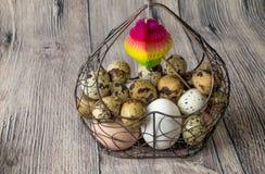 Heel wat kippeneieren en van kwartelseieren liggende metaalstructuur in de vorm van een hart die op een houten lijst liggen Stock Foto