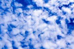Heel wat kleine gescheurde wolken op de achtergrond van de blauwe hemel zijn lichtjes vaag Royalty-vrije Stock Fotografie