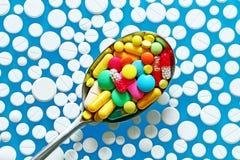 Heel wat kleurrijke pillen in lepel op een blauwe achtergrond Stock Afbeeldingen
