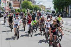 Heel wat mensen en fietsen in de middagfiets berijden, met duidelijke schaduwen royalty-vrije stock fotografie