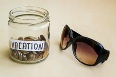Heel wat muntstukken en vakantiewoord in een glaskruik dichtbij zonnebril op een lijst Besparingsgeld voor vakantieconcept royalty-vrije stock afbeelding