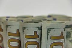 Heel wat rolden de honderd-dollar rekeningen samen met een buistribune naast elkaar in de voorgrond Het concept rijkdom exemplaar stock fotografie