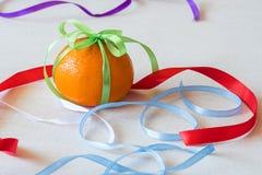Heel wat verschillende gekleurde linten van verschillende kleuren, één bonden als bractic op een sinaasappel Stock Foto's