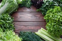 Heel wat verse slabladeren en groenten op een houten lijst met een plaats voor inschrijving stock afbeeldingen