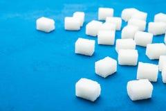 Heel wat verspreide witte kubussen van suiker op een blauwe achtergrond royalty-vrije stock foto