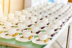 Heel wat witte koffiekoppen en bruine suiker in het seminarie met B stock afbeeldingen