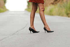 Heels on the road. A pretty woman on a narrow road Royalty Free Stock Photos