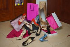 Shoes heels from shop or store in home interior background. Pile of colorful assorted footwear in floor with boxes and package bag stock photo