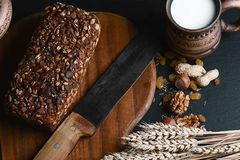 Heelt het samenstellings zwarte brood op de raad, uitstekend mes, melk, tarwevlokken, noten op de lijst en de oude achtergrond, c royalty-vrije stock fotografie