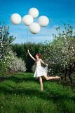 Heerful girl running and jumping laughing in a garden stock images