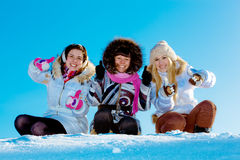 Сheerful girls in snow showing a thumbs up. Group of three young cheerful girl friends outdoors in winter showing a thumbs up Royalty Free Stock Image
