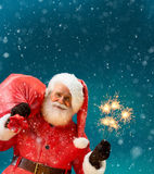 Сheerful Santa Claus with a big bag of gifts and Bengal lights Stock Photo