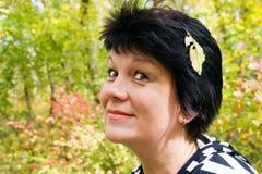 Сheerful woman with autumn sheet on head Royalty Free Stock Photos