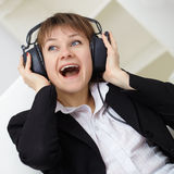 Сheerful woman singing in ear-phones Royalty Free Stock Photo