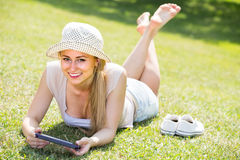 сheerful young barefoot woman holding mobile phone in hands Stock Photo