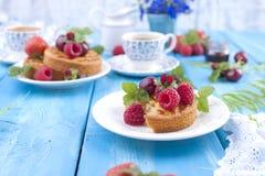 Heerlijk de zomerontbijt, eigengemaakte gebakjes en geurige koffie Op een blauwe houten achtergrond, bessen en groene bladeren en royalty-vrije stock afbeelding