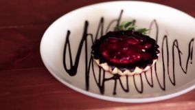 Heerlijk die gebakje met bessen op een plaat met chocoladesaus wordt verfraaid stock video