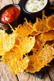 Heerlijk die voorgerecht van de spaanders van de cheddarkaas met kruiden met sausenclose-up worden gediend verticaal royalty-vrije stock afbeelding