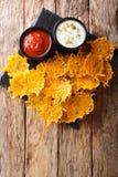Heerlijk die voorgerecht van de spaanders van de cheddarkaas met kruiden met sausenclose-up worden gediend Verticale hoogste meni stock afbeeldingen