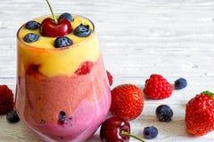 Heerlijk eigengemaakt gelaagd fruit en bessen smoothie dessert in een glas stock afbeeldingen
