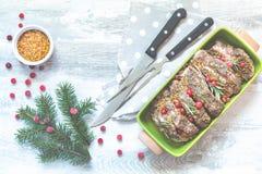 Heerlijk gebakken vlees met Amerikaanse veenbes en kruiden Kerstmislijst altijdgroene tak en bal stock fotografie
