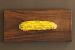 Heerlijk gekookt graan Graan op maïskolf op rustieke houten lijst en wo stock afbeeldingen