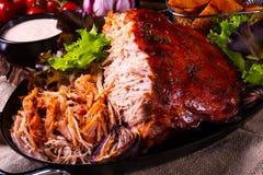 Heerlijk getrokken varkensvlees met aardappel in de schilkwarten stock foto